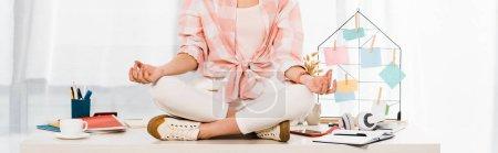 Photo pour Vue partielle de la fille détendue assise dans la pose du lotus sur la table - image libre de droit