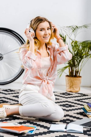 Glad young woman in checkered shirt sitting on carpet and listening music