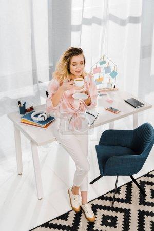 Photo pour Femme détendue en chemise à carreaux buvant du café les yeux fermés sur le lieu de travail - image libre de droit