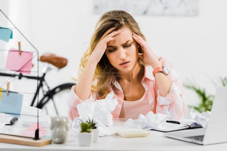 Photo pour Femme blonde sentiment mauvais et touchante la tête avec les yeux fermés sur lieu de travail - image libre de droit