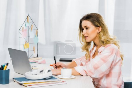 Photo for Curious woman in checkered shirt writing in notebook and looking at laptop - Royalty Free Image