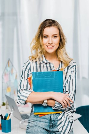 Glad young woman in striped shirt holding notebooks and looking at camera with smile