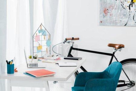 Foto de Oficina en casa acogedora con muebles modernos y bicicleta negro - Imagen libre de derechos