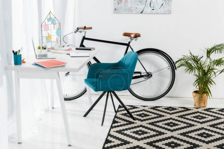 Photo for Cozy home office with furniture, big plant and bicycle - Royalty Free Image