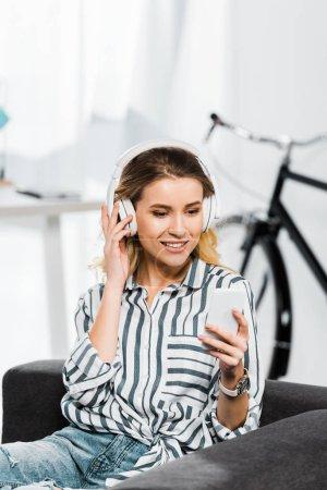 Photo pour Femme joyeuse en chemise rayée tenant smartphone et écoutant de la musique dans les écouteurs - image libre de droit