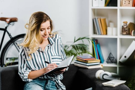 Glad young woman in striped shirt sitting on sofa and writing in notebook