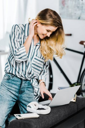 Photo for Charming young woman in striped shirt using laptop at home - Royalty Free Image