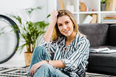glückliche junge Frau in gestreiftem Hemd zu Hause auf Teppich sitzend