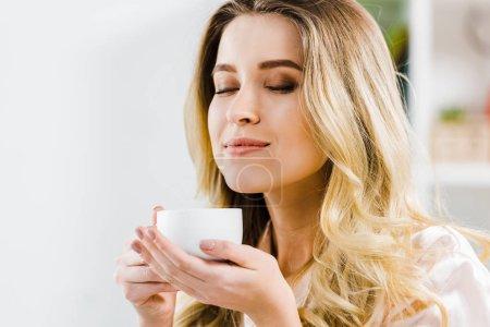 Photo pour Jeune femme détendue tenant une tasse de café avec les yeux fermés - image libre de droit