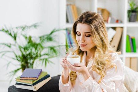 Photo pour Superbe femme bouclée en pyjama, boire du café dans le matin - image libre de droit