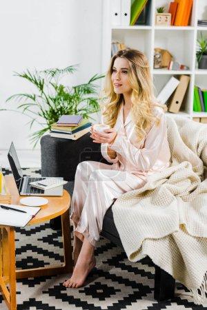 Photo pour Femme détendue en pyjama assise sur le canapé et buvant du café le matin - image libre de droit