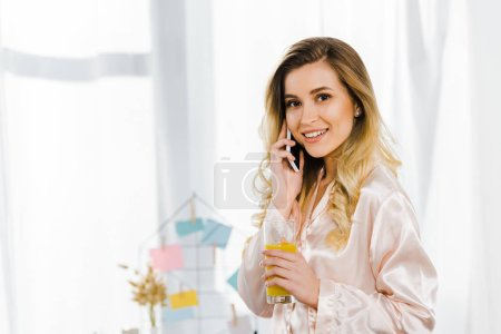 Photo for Attractive woman in satin pyjamas talking on smartphone and drinking orange juice - Royalty Free Image