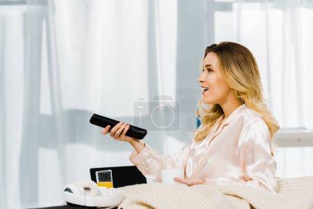 Photo pour Femme souriante en pyjama tenant café tasse et tv de la télécommande - image libre de droit