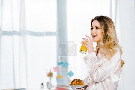 Photo pour Fille inspirée en pyjama tenant croissant et boire du jus d'orange le matin - image libre de droit