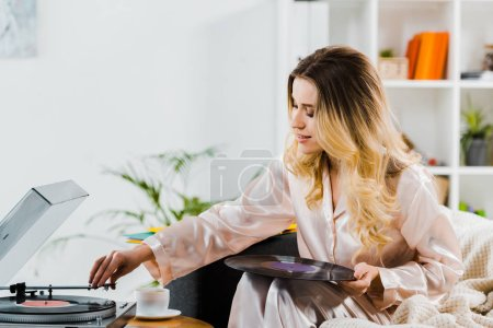 Photo pour Curly femme en pyjama tenant le disque vinyle et à l'aide de gramophone - image libre de droit