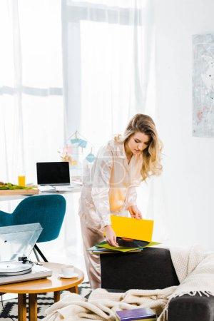 Photo pour Belle jeune femme en pyjama tenant le disque vinyle matin - image libre de droit