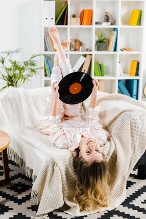 Smiling young woman in pyjamas lying on sofa and holding vinyl record