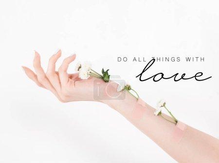 Photo pour Vue recadrée de la femme avec des fleurs sauvages à portée de main sur fond blanc avec faire toutes choses avec l'amour illustration - image libre de droit