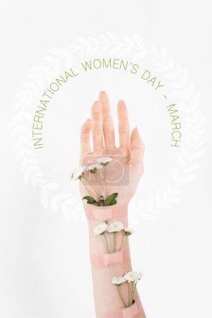 Photo pour Vue recadrée de femme avec des fleurs sauvages sur main sur fond blanc avec une illustration de jour womens international - image libre de droit