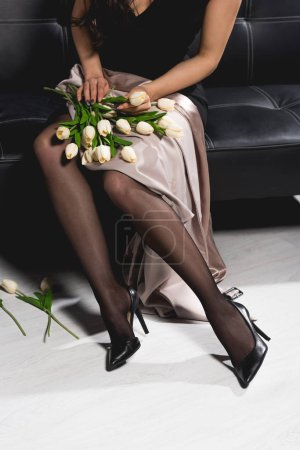 Photo for Cropped view of woman in black dress holding white tulips and sitting on dark couch - Royalty Free Image