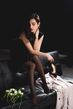 Photo for Attractive woman in black dress sitting on couch with tulips and holding shoes on dark background - Royalty Free Image