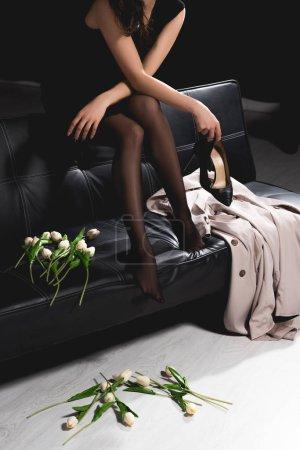 Photo pour Vue recadrée de femme en robe noire assis sur le canapé et la tenue des tulipes blanches sur fond sombre - image libre de droit