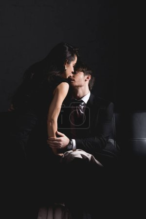 Photo for Man in suit and woman in black dress kissing on couch on dark background - Royalty Free Image