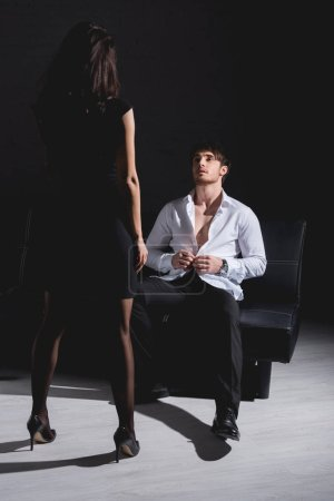 Photo for Brunette woman in black dress standing opposite man undressing and sitting on couch on black background - Royalty Free Image