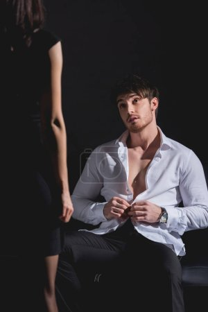 Photo for Selective focus of man undressing and sitting on couch opposite standing woman in dress on black background - Royalty Free Image