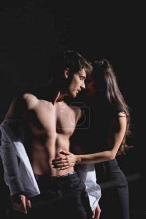 Photo for Woman in dress standing and undressing man in white shirt on black background - Royalty Free Image