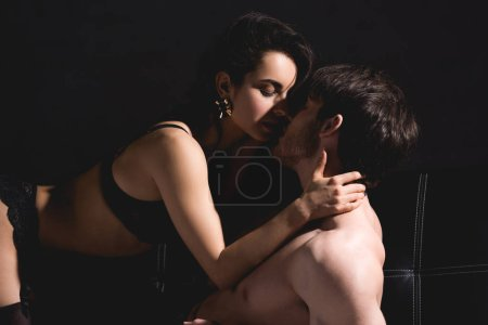 Photo for Shirtless man and woman in black lingerie kissing on couch isolated on black - Royalty Free Image