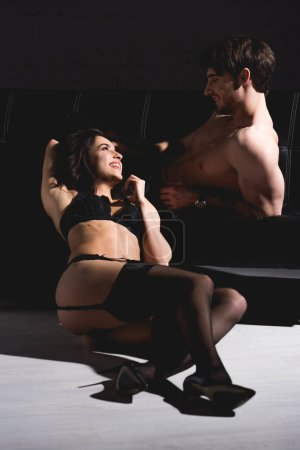 Photo for Attractive woman in black lingerie sitting and smiling on floor and looking to shirtless man on couch on black background - Royalty Free Image