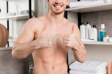 Photo for Cropped view of shirtless man showing thumbs up with hands in bathroom - Royalty Free Image