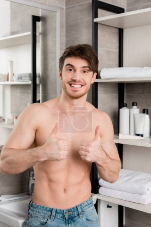 Photo for Handsome shirtless man showing thumbs up with hands and smiling in bathroom - Royalty Free Image
