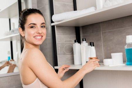 Lächelnde Frau in Spitzenunterwäsche nimmt Kosmetikcreme aus dem Regal im Badezimmer