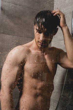 naked and brunette man taking shower in cabin