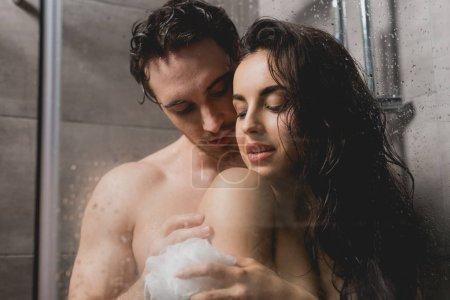 Photo pour Couple sexy embrasser et prendre une douche avec loofah dans la cabine - image libre de droit