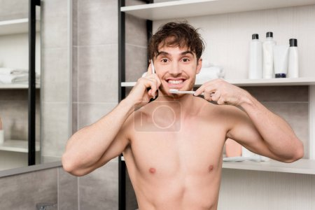 Photo for Smiling man brushing teeth and talking on smartphone in bathroom - Royalty Free Image