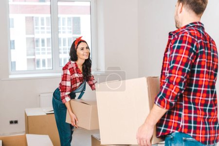 Photo pour Femme heureuse tenant boîte et regardant l'homme à la maison - image libre de droit