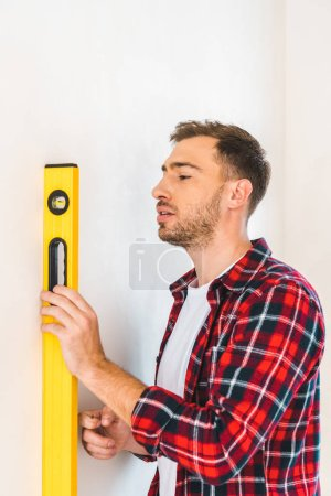 Photo for Handsome man holding measuring level while measuring wall at home - Royalty Free Image