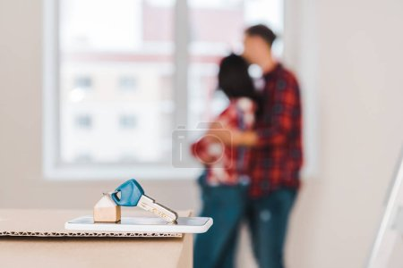 Photo for Selective focus of key lying on smartphone and box with couple hugging on background - Royalty Free Image