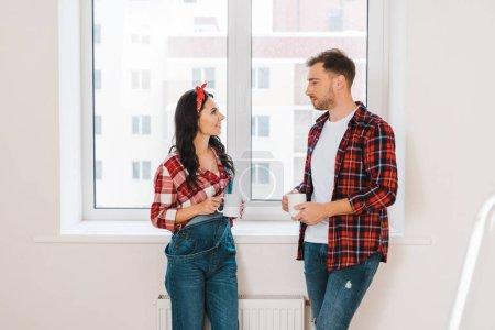 Photo pour Attrayant femme et bel homme tenant des tasses à la maison - image libre de droit