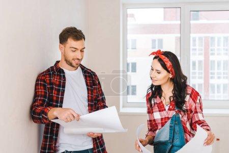Photo pour Homme gai debout avec un plan près de petite amie attrayante à la maison - image libre de droit