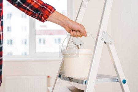 Photo pour Vue recadrée d'un homme tenant un seau de peinture à la main sur une échelle - image libre de droit