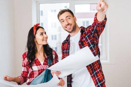 Photo pour Belle femme regardant l'homme pointant du doigt tout en tenant le plan à la maison - image libre de droit