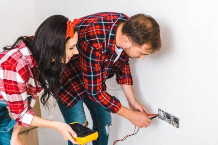 Photo for Cheerful woman holding digital multimeter near boyfriend looking at power socket - Royalty Free Image