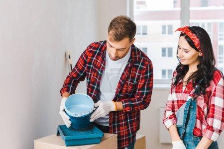 hombre sosteniendo cubo de pintura con pintura azul cerca de la mujer usando guantes en casa