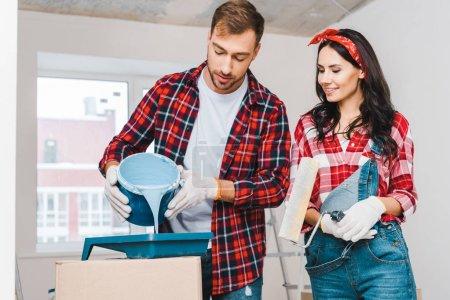 Foto de Hombre guapo verter pintura cubo con pintura azul junto a la alegre mujer rodillo - Imagen libre de derechos