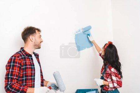 Foto de Pared de pintura de mujer en color azul junto a la alegre novio en casa - Imagen libre de derechos