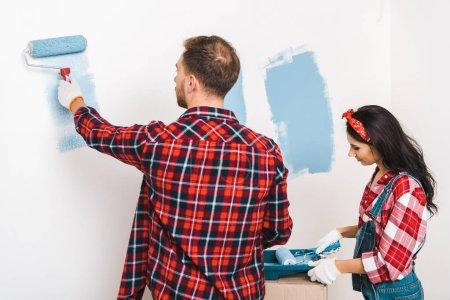 Foto de Hombre y mujer de la pintura de la pared en color azul en casa - Imagen libre de derechos